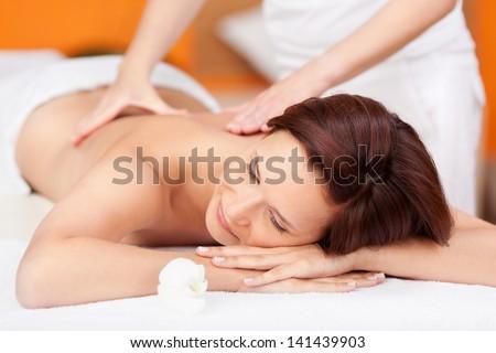 Portrait of sexy fresh woman in spa salon getting massage - stock photo