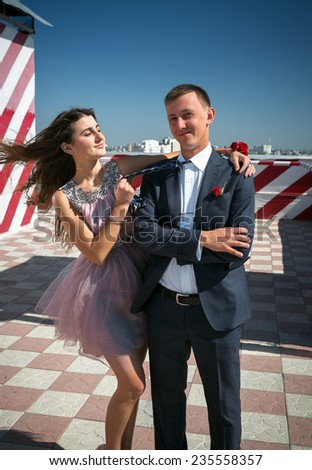Portrait of sexy girl hugging boyfriend on roof top at windy day - stock photo