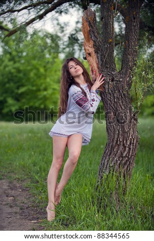 Portrait of sexy, lovely young girl in a beautiful national shirt standing next to a tree in an outdoor - stock photo