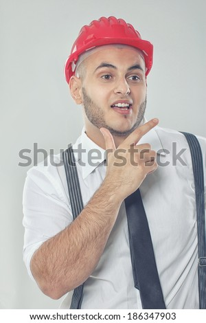 Portrait of sexy man posing in studio in red helmet - stock photo