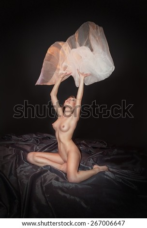 Portrait of sexy nude woman on a black silk - stock photo