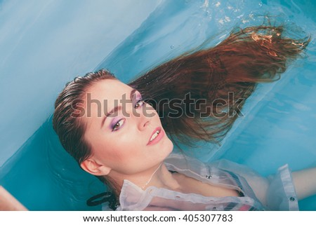 Portrait of sexy seductive woman floating in swimming pool water. Pretty alluring young girl wearing wet white shirt. Top view. - stock photo