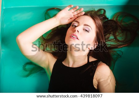 Portrait of sexy seductive woman wearing black dress in swimming pool water. Young attractive alluring girl floating. Top view. - stock photo