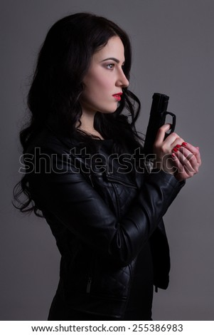 portrait of sexy woman in black with gun over grey background - stock photo