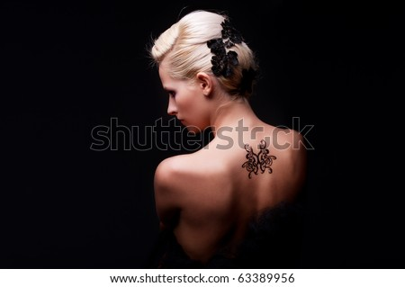 portrait of sexy woman with tattoo on her back - stock photo