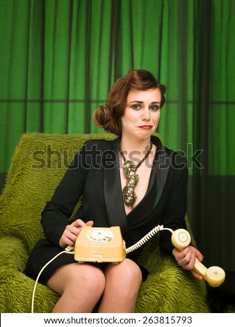 portrait of sexy young fashion model sitting on armchair, holding retro telephone, pensive expression - stock photo