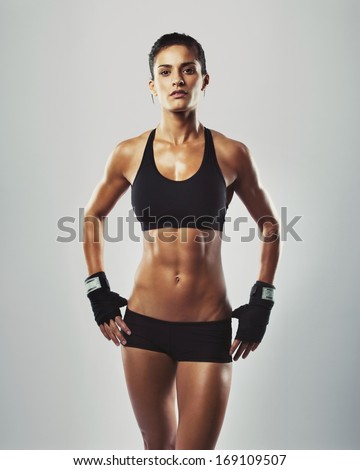 Portrait of sexy young woman with her hands on hips looking at camera. Fitness female with muscular body ready wearing hand gloves for workout on grey background - stock photo