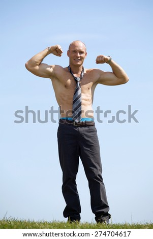 Portrait of shirtless bald young man wearing tie holds his arms up in park - stock photo