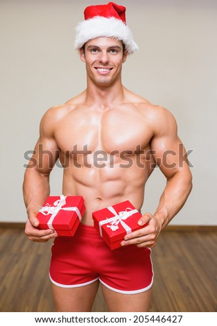 Portrait of shirtless macho man in santa hat holding gifts - stock photo