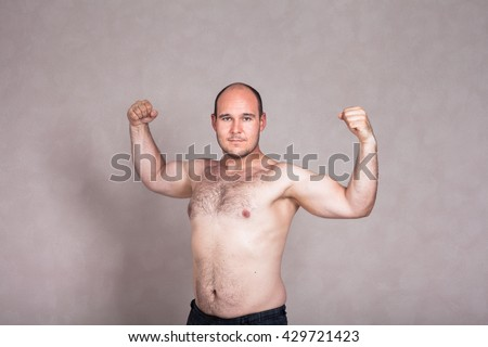 Portrait of shirtless man posing and showing his strong arms and hairy body. - stock photo