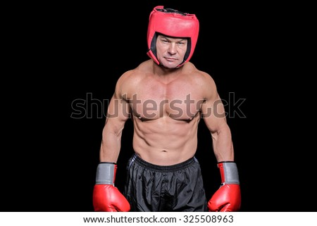 Portrait of shirtless man with boxing headgear and gloves against black background - stock photo