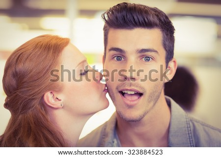 Portrait of shocked businessman being kissed by woman in creative office - stock photo