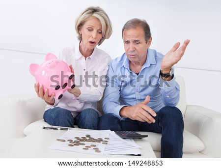 Portrait Of Shocked Couple Holding Piggybank At Home - stock photo