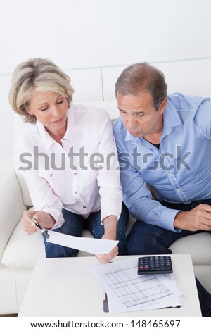 Portrait Of Shocked Couple Sitting On Couch Looking At Bill - stock photo