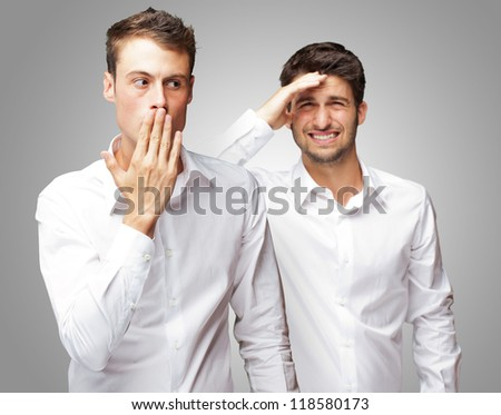 Portrait Of Shocked Man In Front Of Frustrated Man Isolated On Gray Background - stock photo