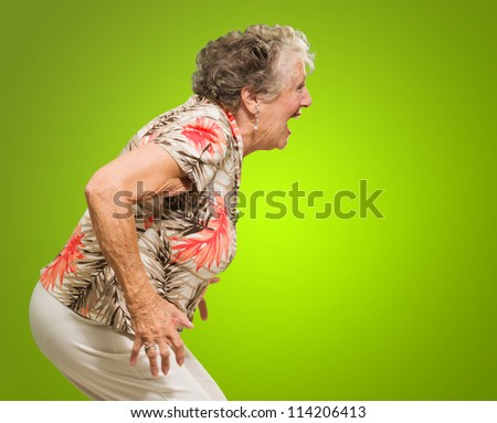 Portrait Of Shocked Senior Woman On Green Background - stock photo