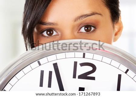 Portrait of shocked woman with clock - stock photo