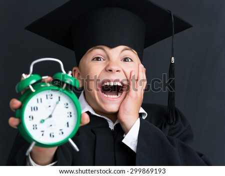 Portrait of shocked young boy Bachelor with alarm-clock looking at camera at the black chalkboard in classroom - stock photo
