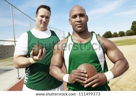 Portrait of shot putters holding shot put and discus on track - stock photo
