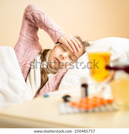 Portrait of sick girl lying in bed and holding hand on head - stock photo