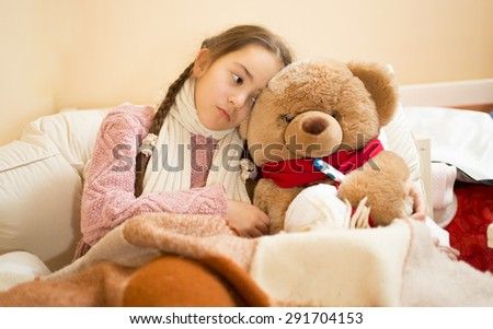 Portrait of sick girl resting in bed with brown teddy bear - stock photo