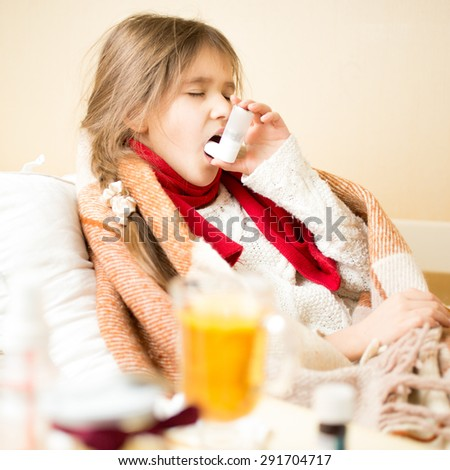 Portrait of sick girl with respiratory illness lying in bed and using inhaler - stock photo