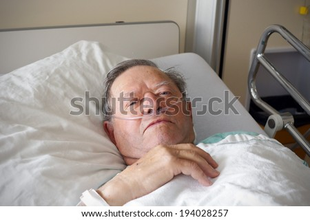 Portrait of sick old man in hospital bed - stock photo
