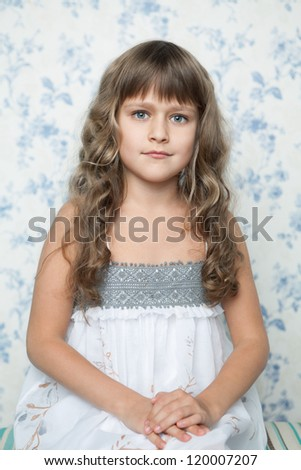 Portrait of sincere cheerful tender young blond girl child with grey eyes and wavy long hair in sitting posture looking at camera - stock photo