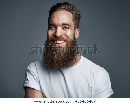 Portrait of single bearded handsome young Caucasian man with big smile and white short sleeve shirt over gray background - stock photo