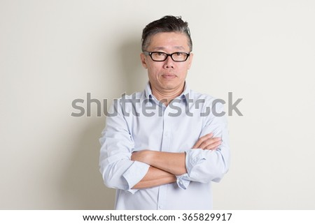 Portrait of single mature 50s Asian man in casual business arms crossed and standing over plain background with shadow. - stock photo