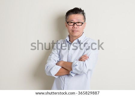 Portrait of single mature 50s Asian man in casual business arms crossed smiling and standing over plain background with shadow. - stock photo