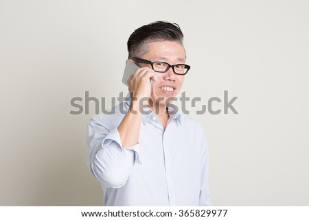 Portrait of single mature 50s Asian man in casual business making a call using smartphone and smiling, standing over plain background with shadow. Chinese senior male people. - stock photo
