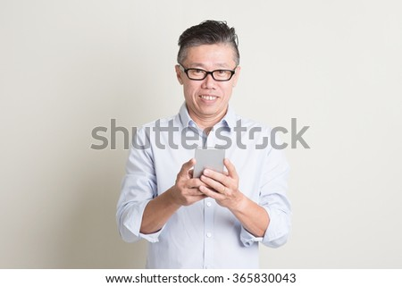 Portrait of single mature 50s Asian man in casual business using mobile applications on smartphone and smiling, standing over plain background with shadow. Chinese senior male people. - stock photo