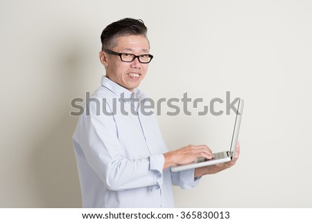 Portrait of single mature 50s Asian man in casual business using notebook pc and smiling, standing over plain background with shadow. Chinese senior male people. - stock photo