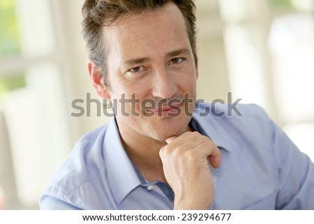 Portrait of single middle-aged man sitting in sofa - stock photo