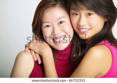 Portrait of sisters hugging - stock photo