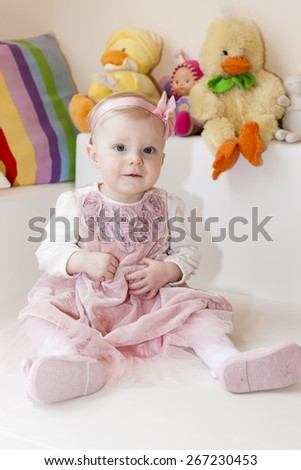 portrait of sitting toddler girl wearing pink dress - stock photo