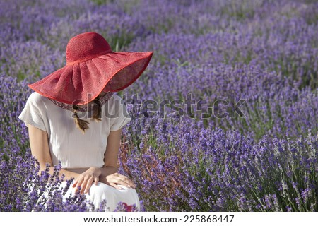 Portrait of sitting woman in the field of blossoming lavender - stock photo