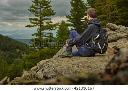 Portrait of sitting young man while hiking across macedonia mountains in prespa national park having pleasure with nice view - stock photo