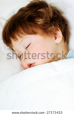 portrait of sleeping child in white bed - stock photo