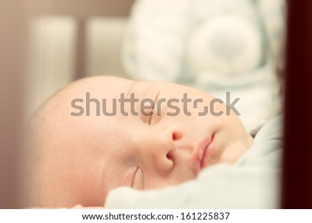 Portrait of sleeping newborn baby,view through the fence at the crib. - stock photo