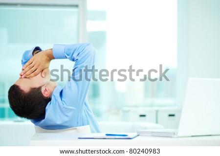 Portrait of sleepy businessman yawning in office - stock photo