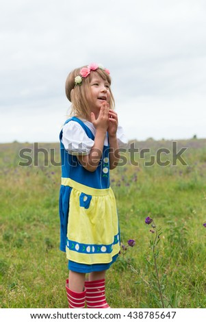 portrait of small adorable blond girl wearing traditional swedish national folk costume in blue and yellow colors on midsummer celebration  - stock photo