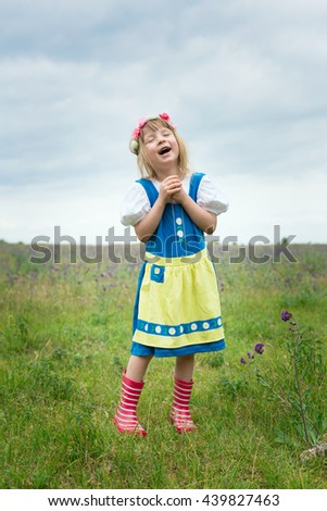 portrait of small adorable blond girl wearing traditional swedish national folk costume in blue and yellow colors on midsummer celebration and singing - stock photo