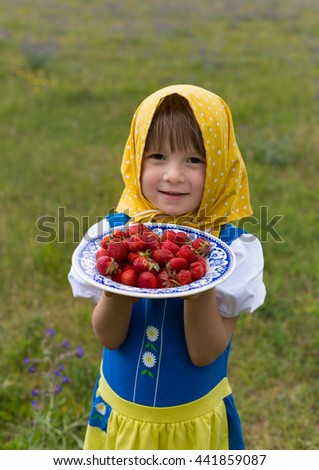 portrait of small adorable blond girl wearing traditional swedish national folk costume in blue and yellow colors on midsummer celebration and holding plate with fresh strawberries - stock photo