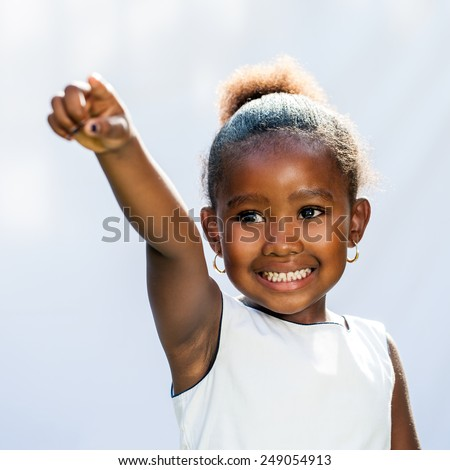 Portrait of small African girl pointing with finger into distance.Isolated against light background. - stock photo