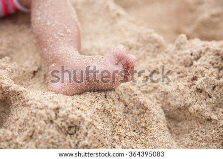 portrait of small baby feet on a sand - stock photo