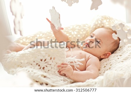 Portrait of small cute girl with blue eyes in her cozy white bed. Winter mood. - stock photo