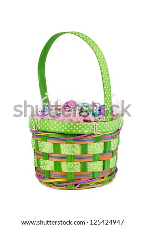 Portrait of small green basket with Easter eggs and chocolate over the white background - stock photo