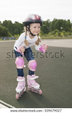 portrait of small little caucasian blond girl skating outside on stadium track in protective helmet - stock photo